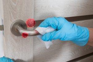 bigstock_Wiping_Door_Knob_With_Antibact_359151226